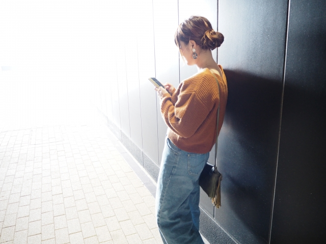 スマホを見ながら待っている女性イメージ