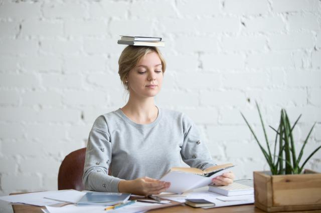 頭の上に本を乗せて正しい頭の位置をキープする女性イメージ